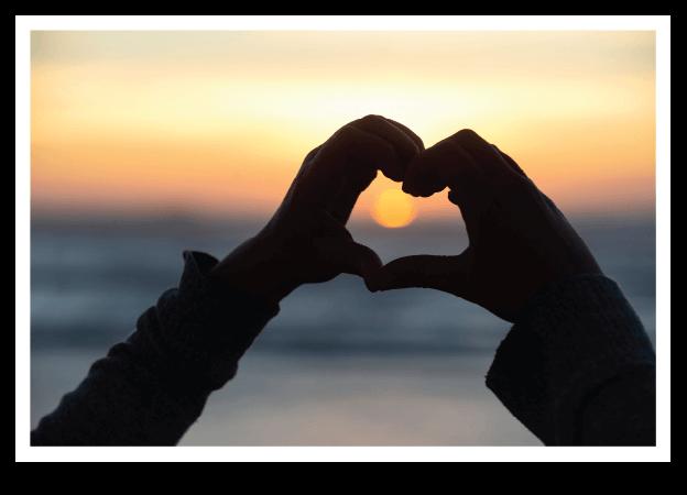 Hand heart around setting sun